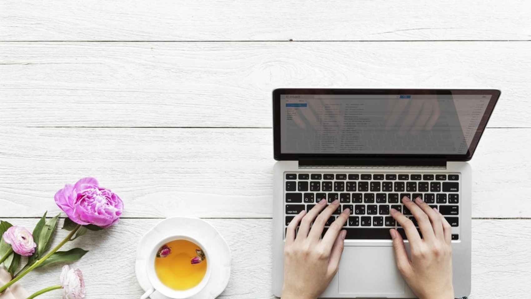 a cup of coffee and flowers beside a girl typing in her laptop to boost her content marketing plans