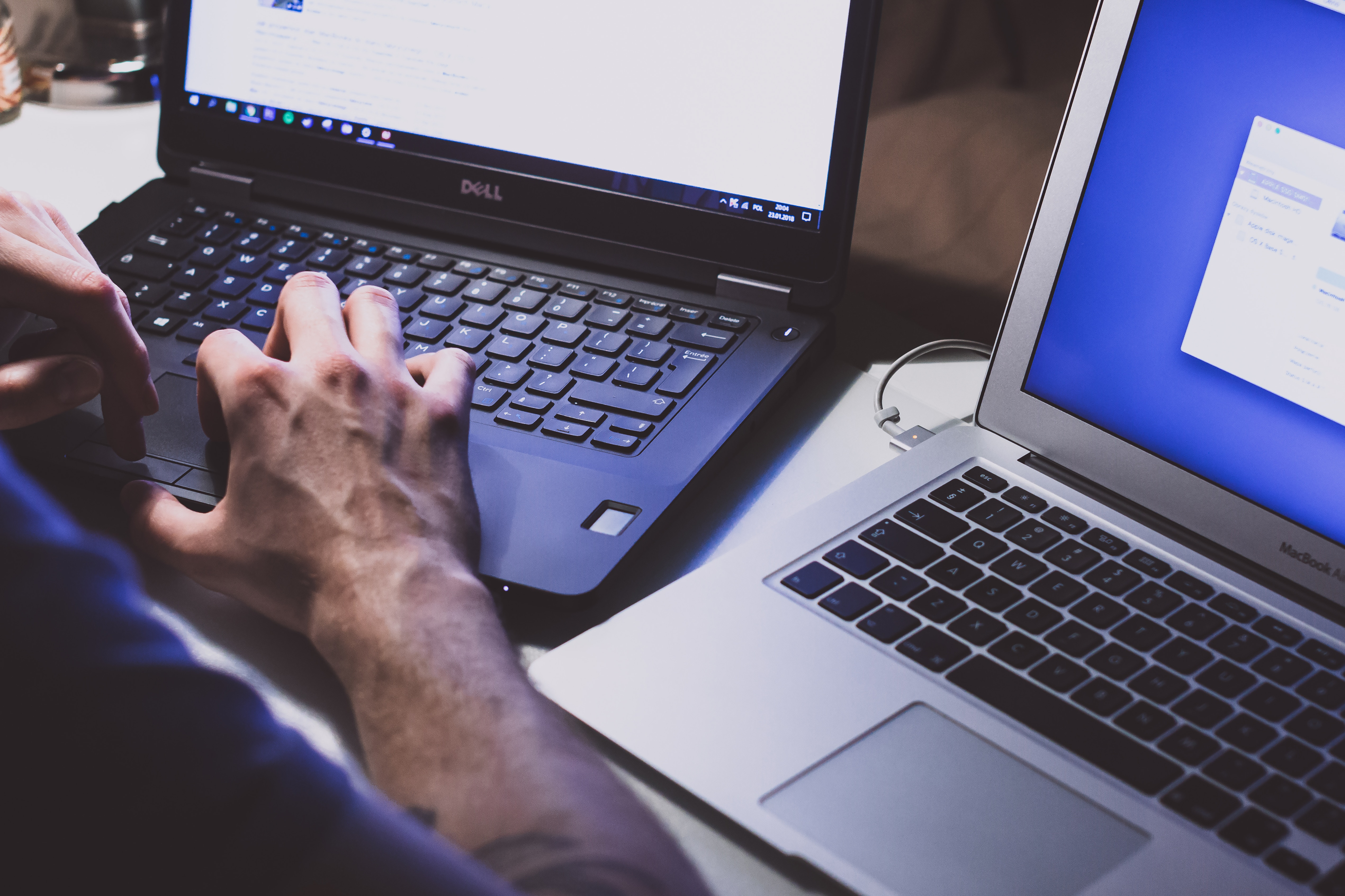 a man working with two laptops, skilled employees are included in the outsourcing hacks