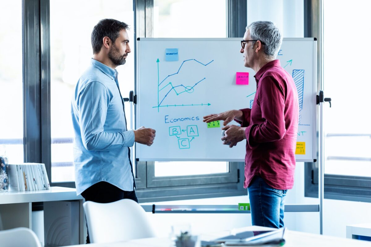 two businessmen discussing data on whiteboard